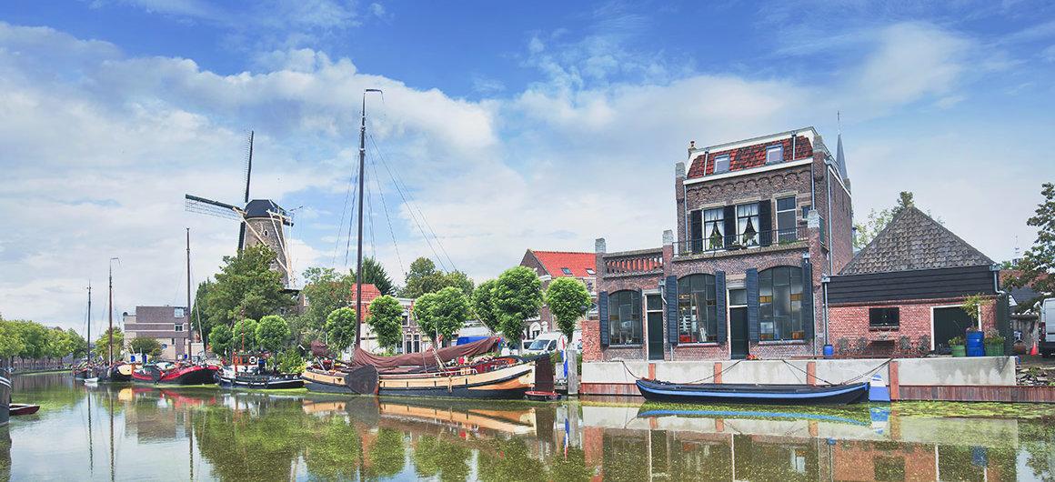 Boten op het kanaal en windmolen, Gouda