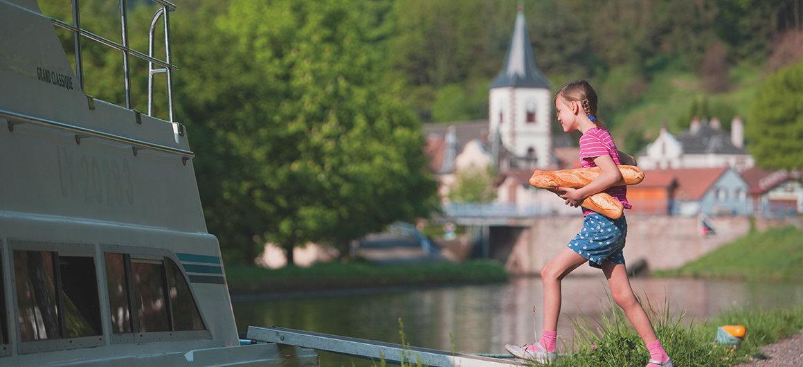 Het meisje brengt verse baguette aan boord